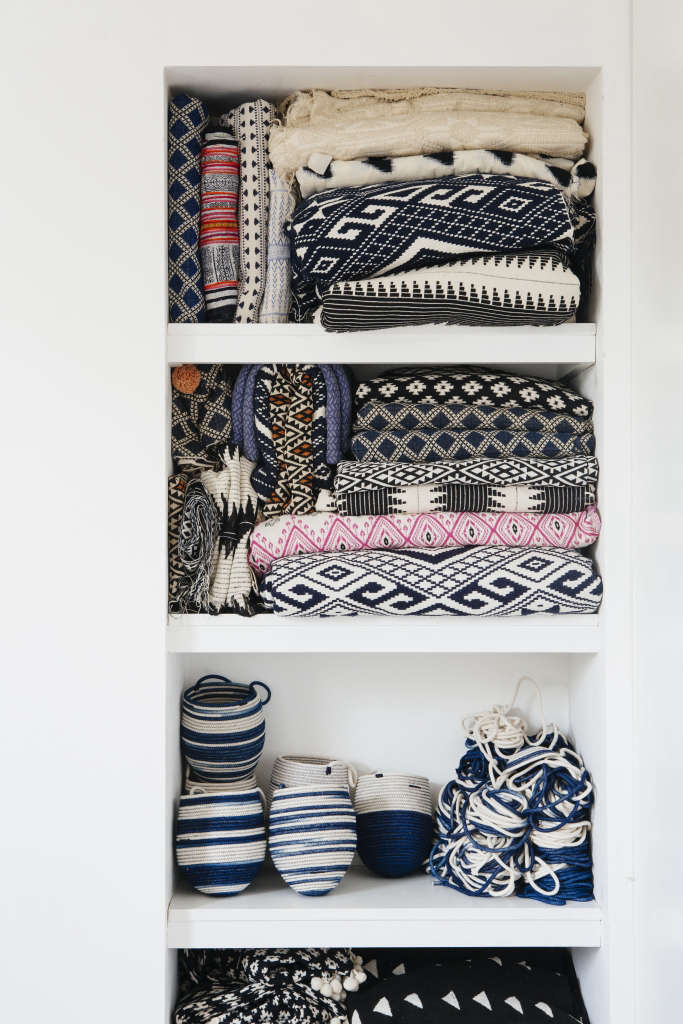 Blankets and baskets, ready to be sold, are efficiently stored in built-in shelving. Ash sources her fabrics from Mali and India; the feather padding for the cushions is responsibly sourced from a company in Sussex that is RDS (Responsible Down Standard) certified, which guarantees that the birds have not been mistreated.