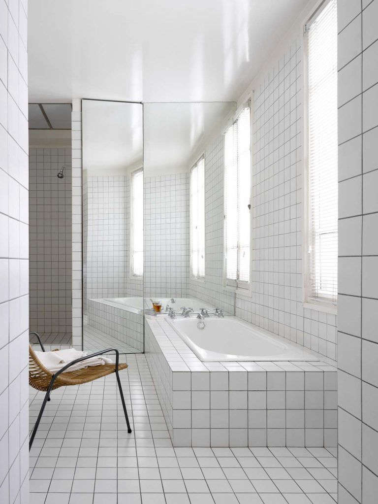An artful built-in bath, surrounded in the same tile as the floor and walls, in A Minimalist Parisian Loft. Photograph from RL Interior Architecture.
