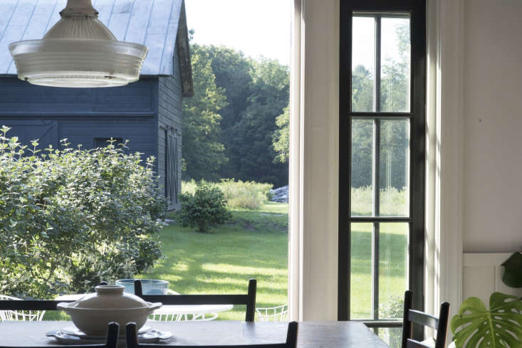 The dining room looks out to the renovated barn, now painted in Sherwin Williams&#8