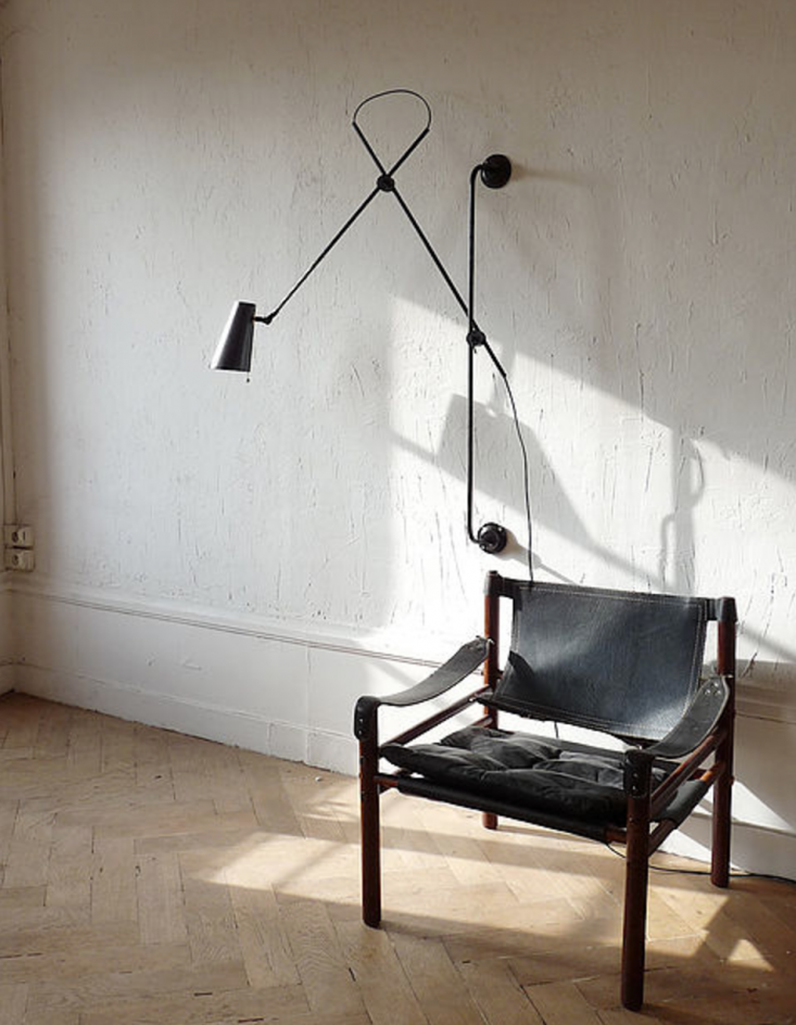 The Adjustable Two Arms Wall Lamp can be affixed at different heights along a vertical rail; €659 ($700).