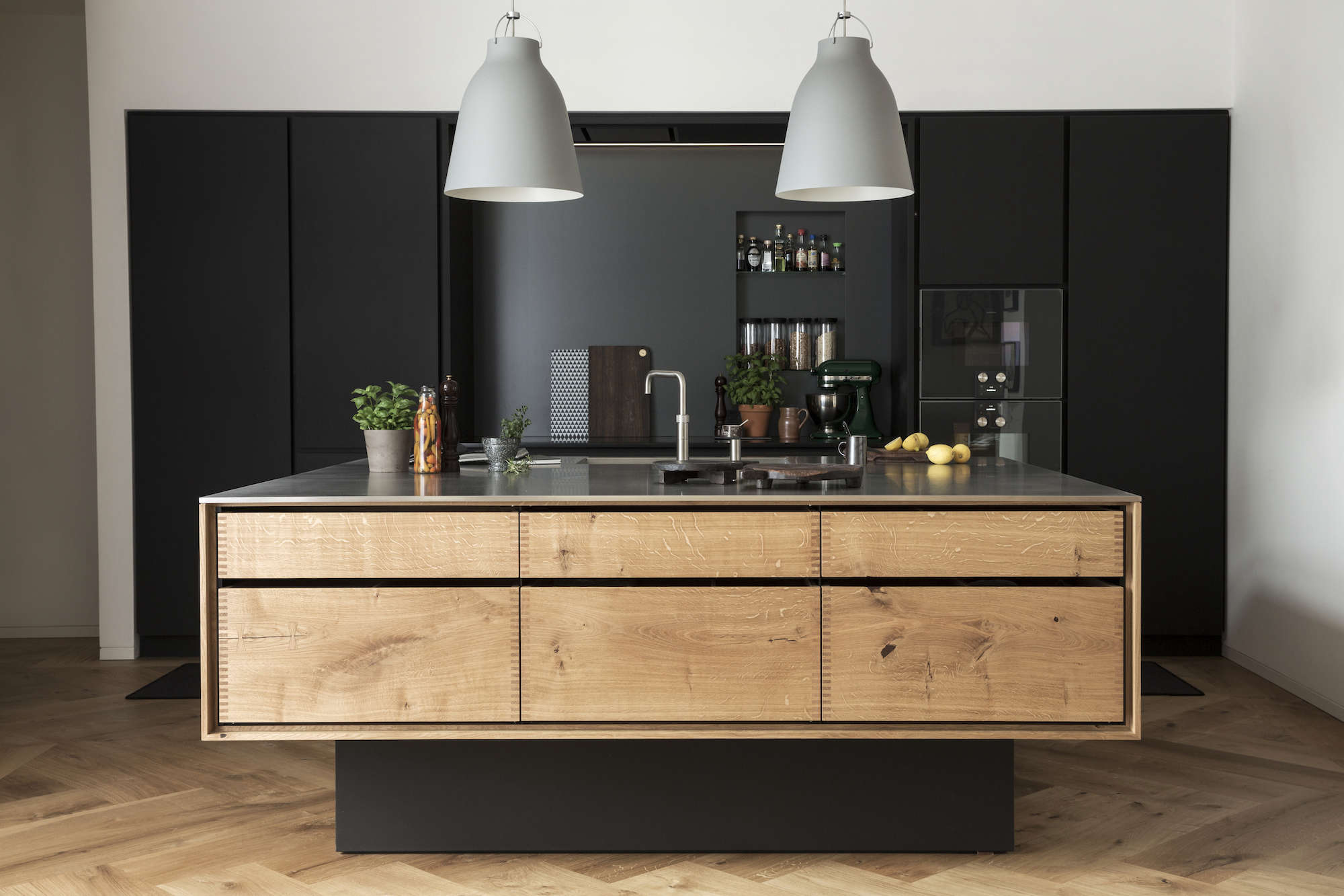 wood-island-kitchen-gray-pendant-lights-black-backsplash-denmark-garde-Hvalsoe