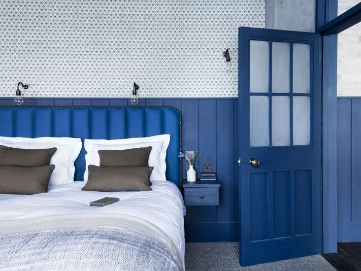 the bedroom is a symphony of blue and white. the custom headboard is upholstere 16
