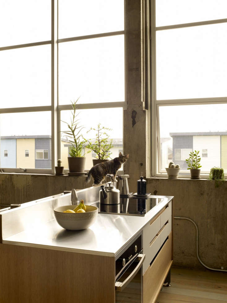 the kitchen island worktop is stainless steel with a bent steel backsplash. a \ 13