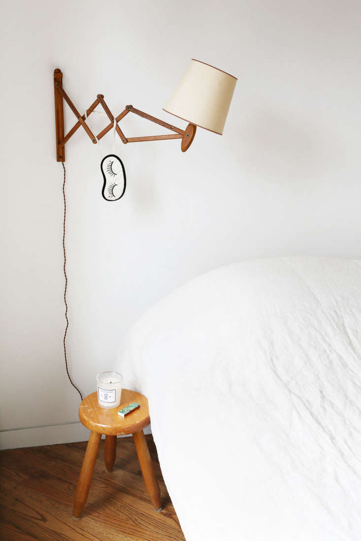 Javitch keeps a few wellness essentials by the bed: a candleand long matches. A sleep mask hangs from a vintage accordion wall lamp from Orange Furniture in LA.