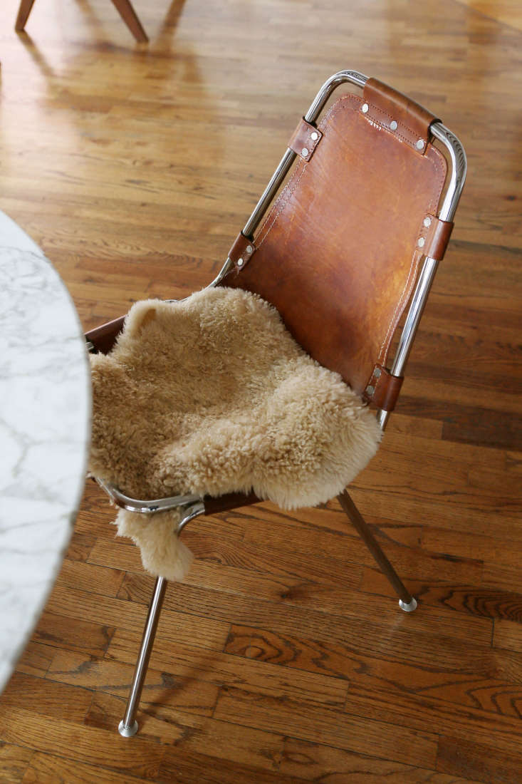 Leather sling dining chairs with swatches of fur add texture.