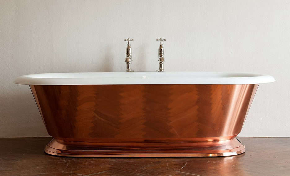 Drummonds Copper Tay Bath is a large doubled-ended rolltop tub wrapped in sheets of pure copper that are hand-pressed onto the cast iron base. Available as polished (shown) or burnished copper at Drummonds in the UK. Contact Drummonds for pricing.