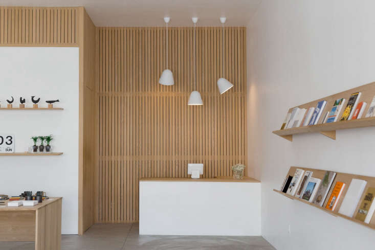 the shop is outfitted minimally, withwhite walls, wood storage, andconcrete 9