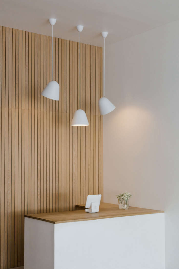 tilt pendant lights by nyta hang above the counter. the countertop isan untre 10
