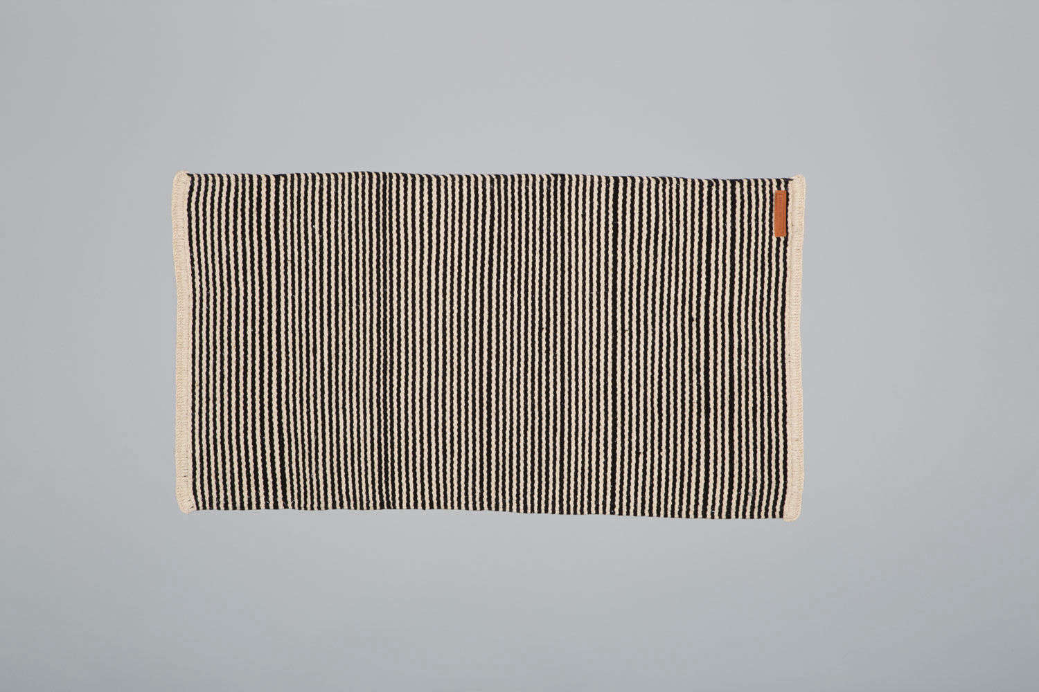 The new Breton Rug Small is a wool rug made up of black and cream stripes, like a Breton striped shirt.