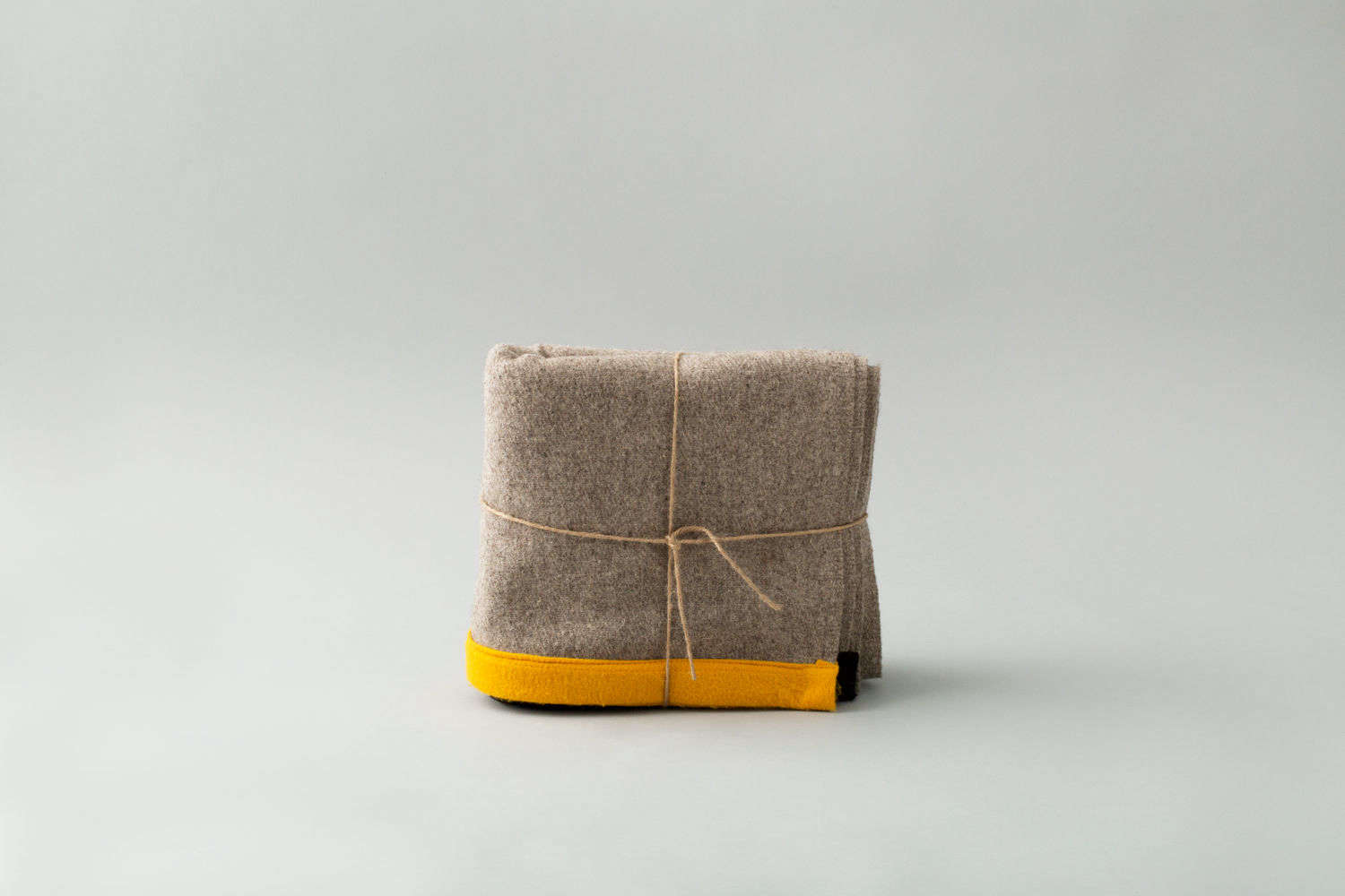 The Lagos del Mundo Throw is made of gray wool with a yellow border.