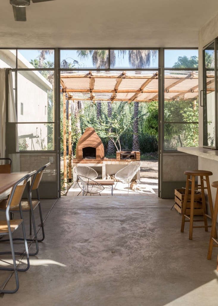 The kitchen opens onto a shaded outdoor lounging area with Acapulco Chairs. (For something similar, try the Handmade Woven Acapulco Lounge Chair, currently on Overstock.)