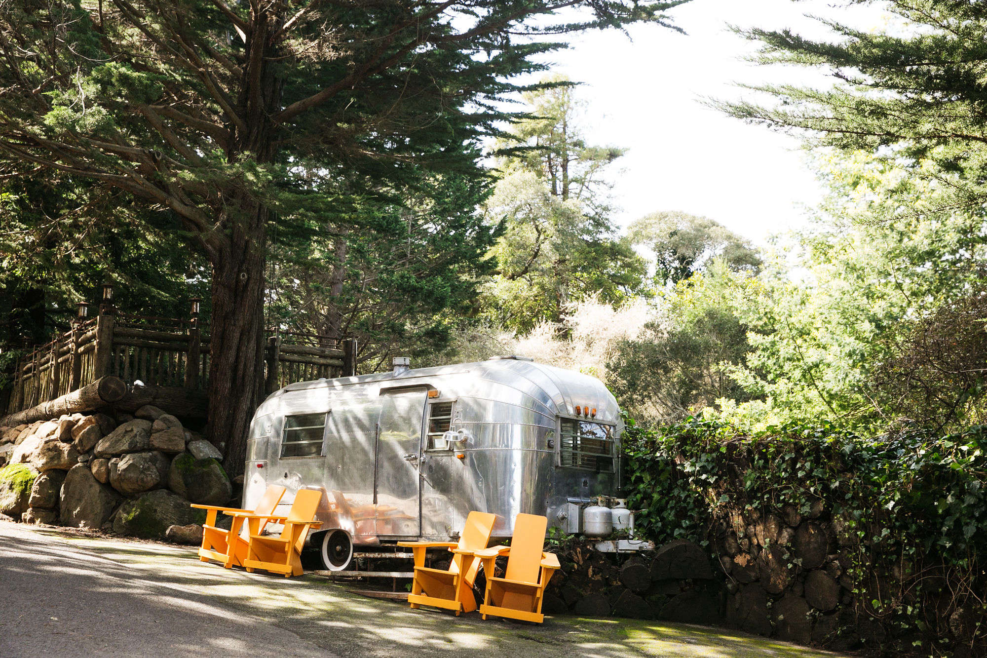 an airstream trailer and orange lounge chairs marks the entrance to the manka&a 9