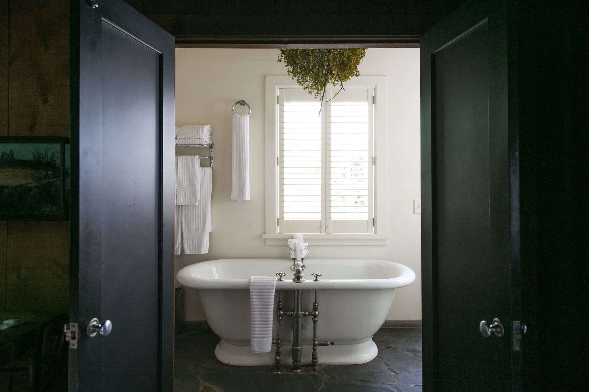 a ball of foraged mistletoe hangs above the freestanding tub in the cabin& 24
