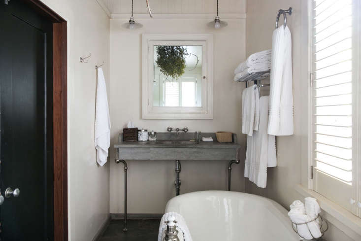 A cast concrete sink looks almost delicate in an en suite bathroom at Manka&#8