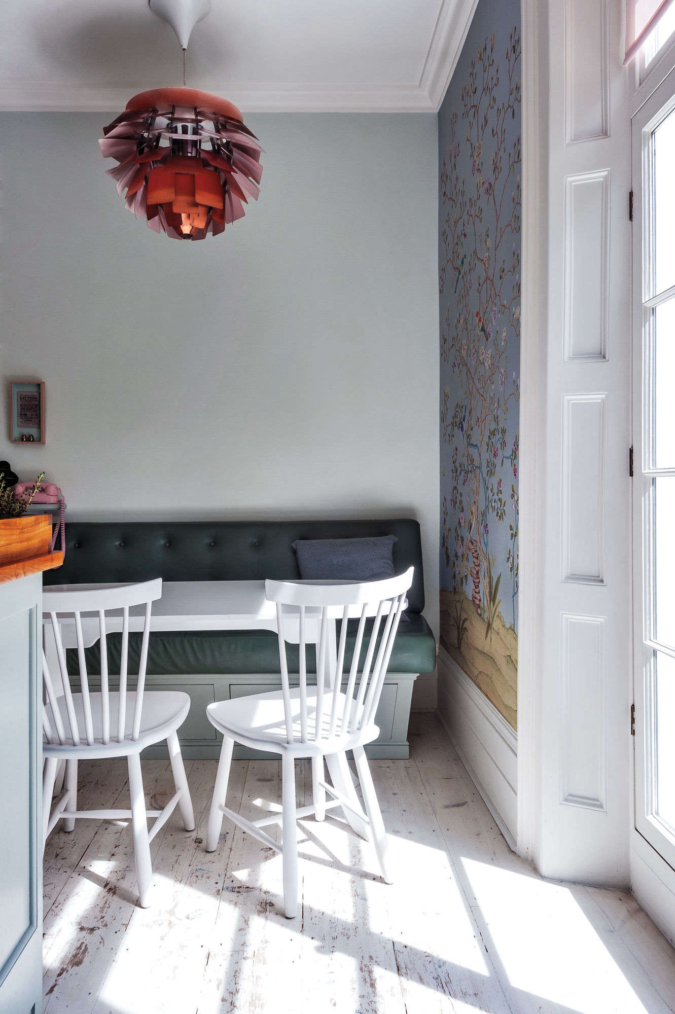 Pale blue walls, Chinoiserie wallpaper, Swedish chairs, and retro accents come together at the breakfast table in the kitchen.Photograph by Matthew Williams for Remodelista: A Manual for the Considered Home.