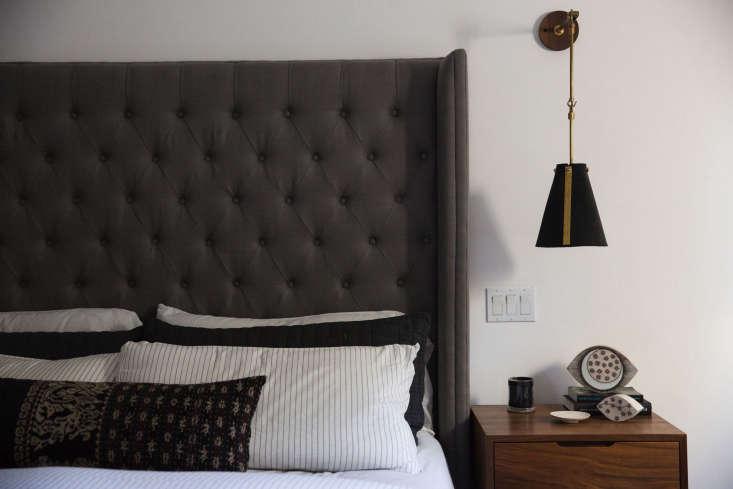 a dark gray headboard adds drama. the long pillow is drost&#8\2\17;s own de 22