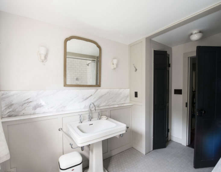 The bathroom is anchored by a vintage porcelain pedestalsink. Walls are painted in Benjamin Moore Pale Oak with millwork in complementary Revere Pewter.