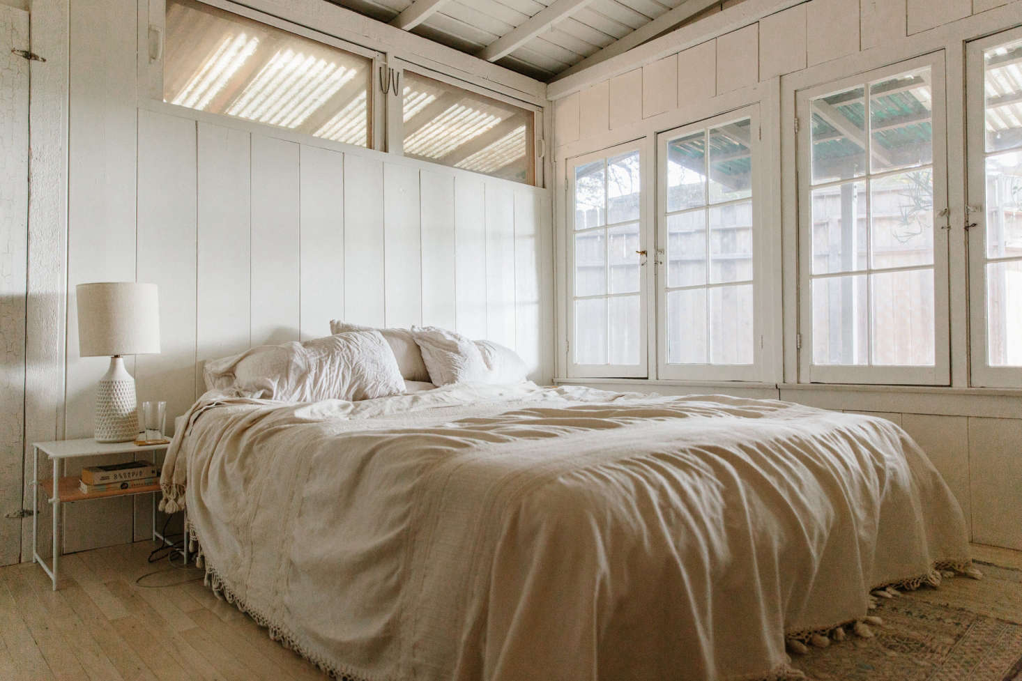 The master bedroom—cream walls, cream bedding, ceramic lightingin cream—has an easy undone look. Adding to the texture: a nightstand with leather sling shelf, shiplap walls (see Expert Advice: The Enduring Appeal of Shiplap), and relaxed linens.