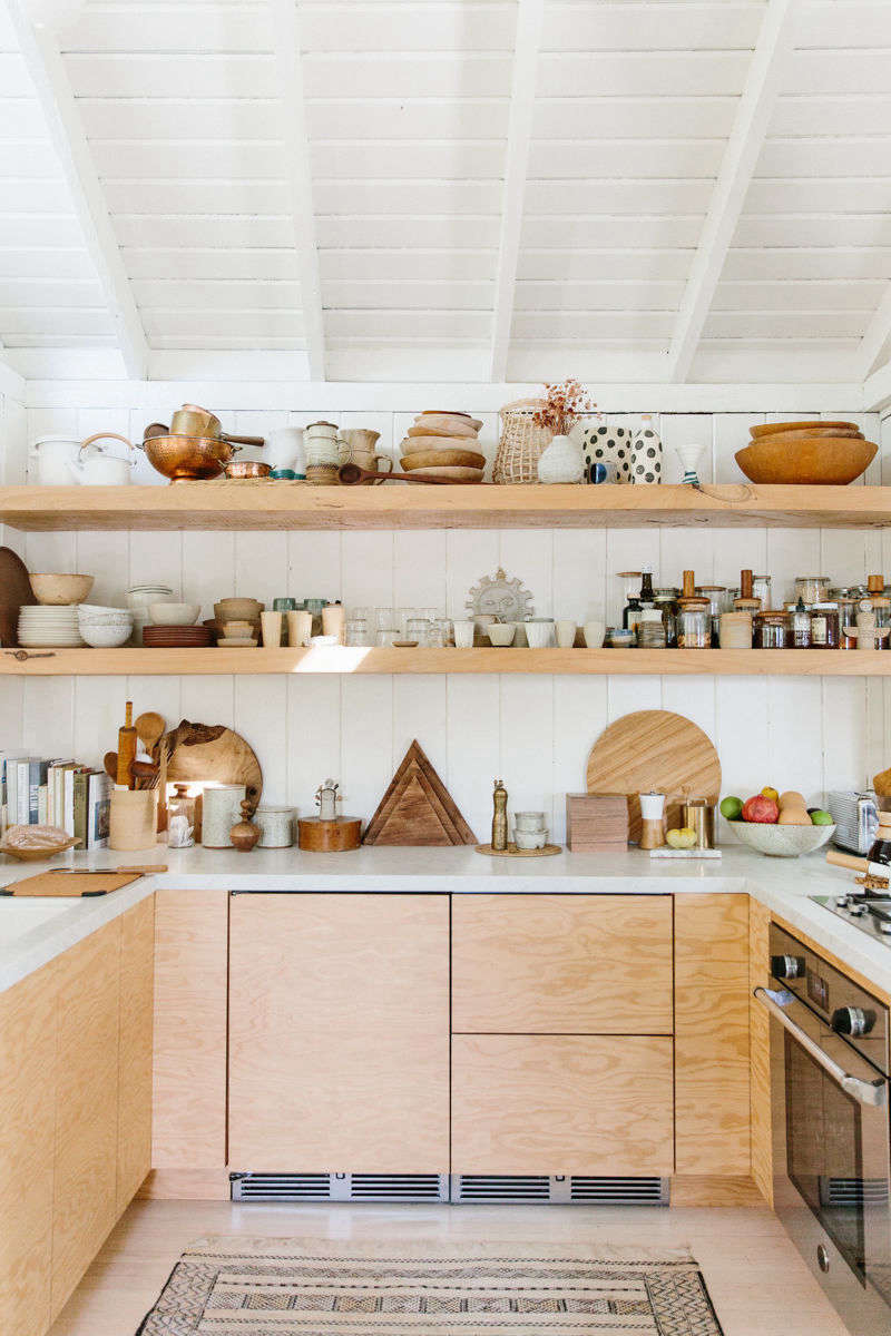 The finished kitchen: streamlined and compact, but chock-full ofceramics, wooden bowls, and copper colanders.