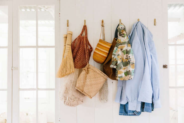 near the kitchen, brass hooks by counter space hold small brooms and market bag 13