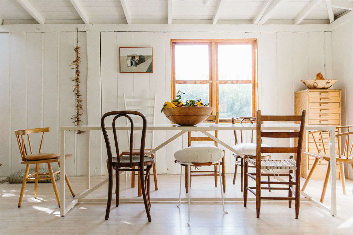 The kitchen opens to a wide, bright dining room, where mismatched wooden chairs—some with oversize cushions—surround the table.