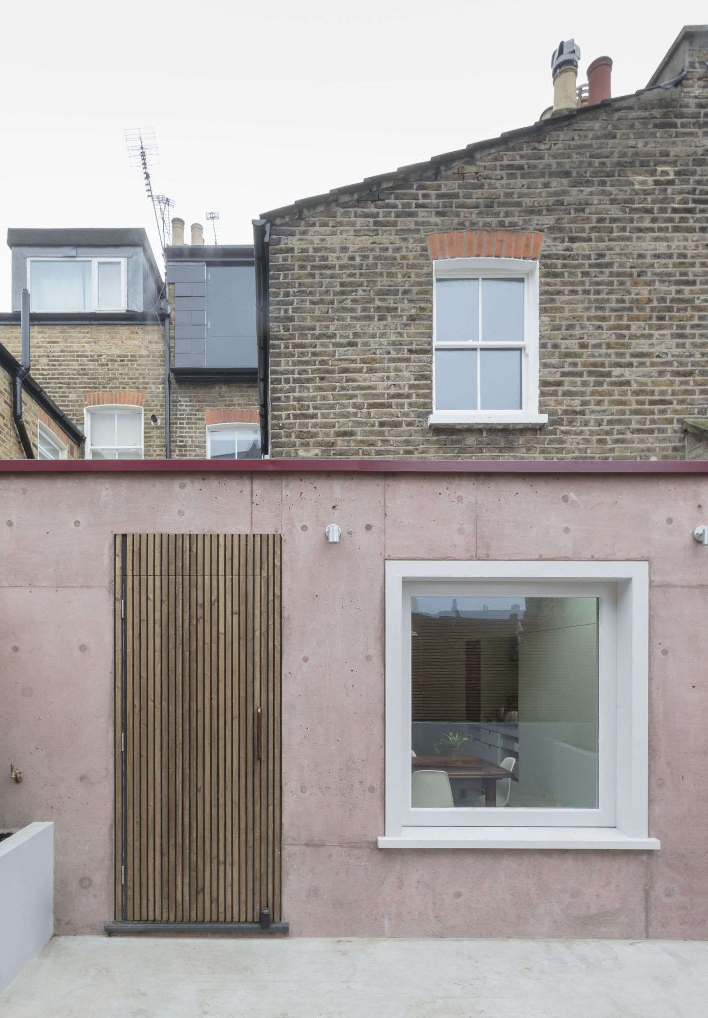 Situated in the back of the house, the six-square-meter (64.5-square-foot) extension features a pigmented cast concrete wall with a slatted wood door and integrated sliding glass window. The new courtyard—shown pre-plantings (it&#8