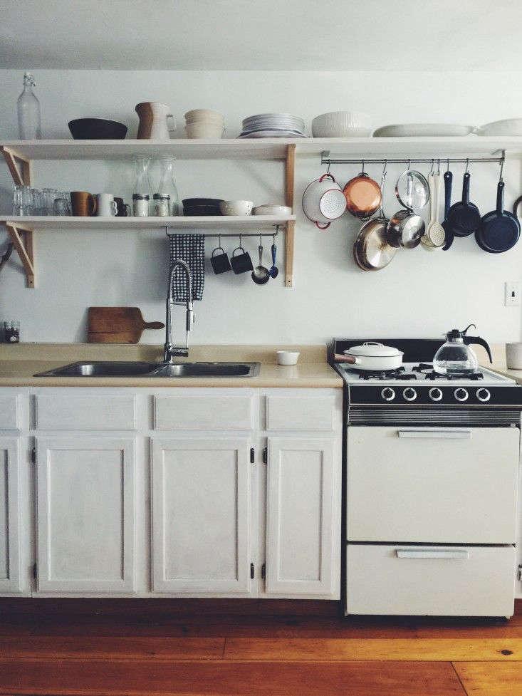 A utensil rail mounted to the underside of an open shelf in ceramic artist Suzie Ryu&#8