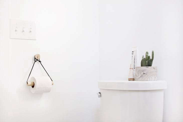 Manda from the Merry Thought created a DIY Toilet Paper Holder with a wooden knob, leather string, and a dowel.