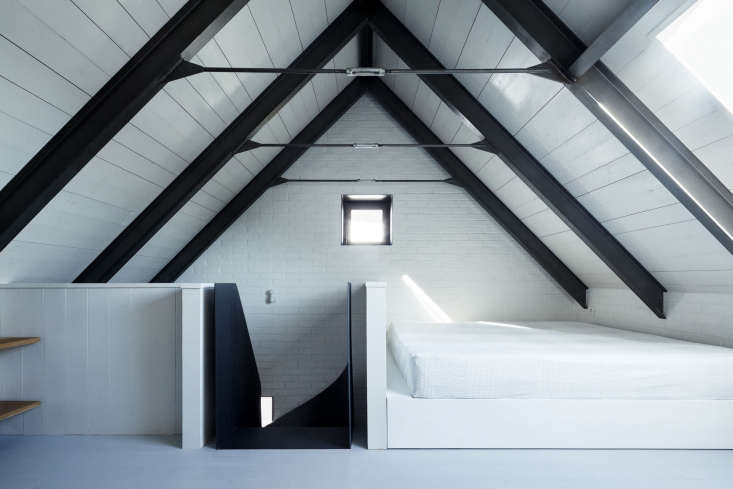 in another attic room, a simple white mattress fits into a nook abovethe stai 15