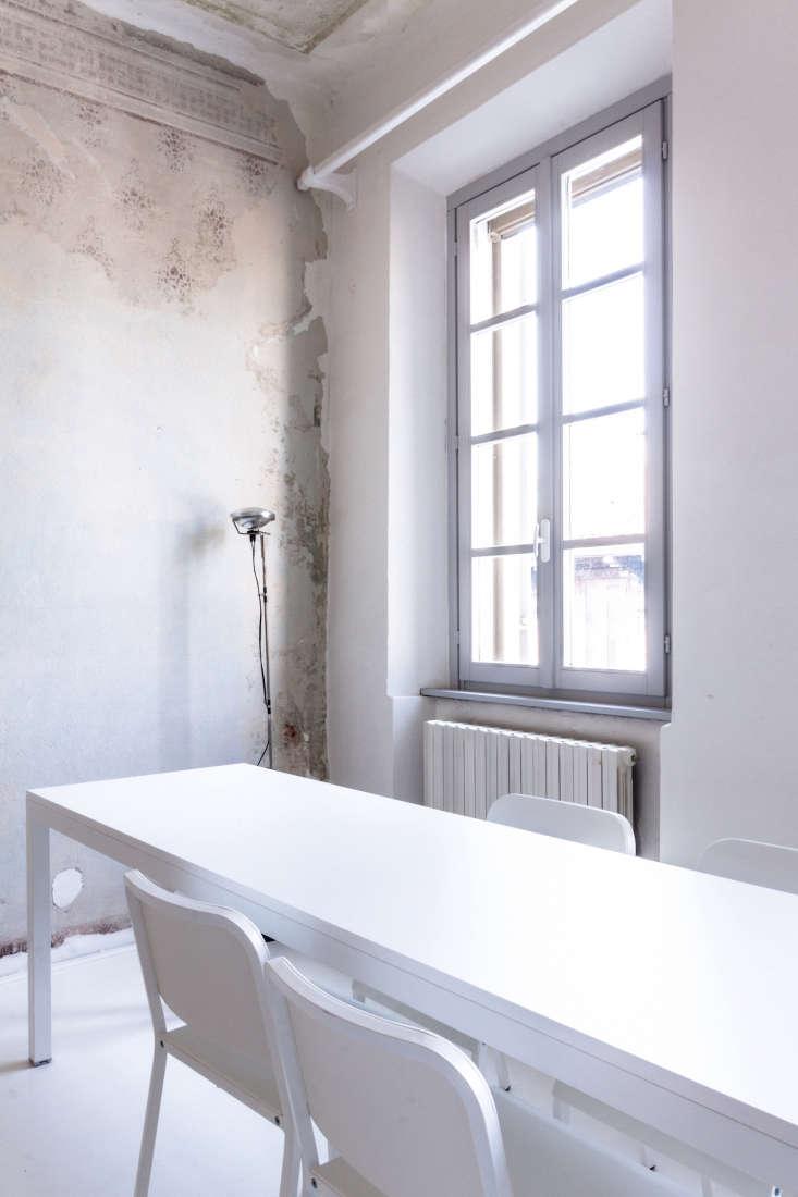 all white apartment modern table white chairs scraped wallpaper walls archiplan studio