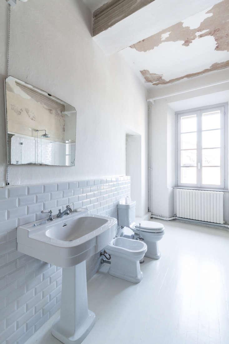 all white bathroom apartment italy ceramic tile wainscot archiplan studio