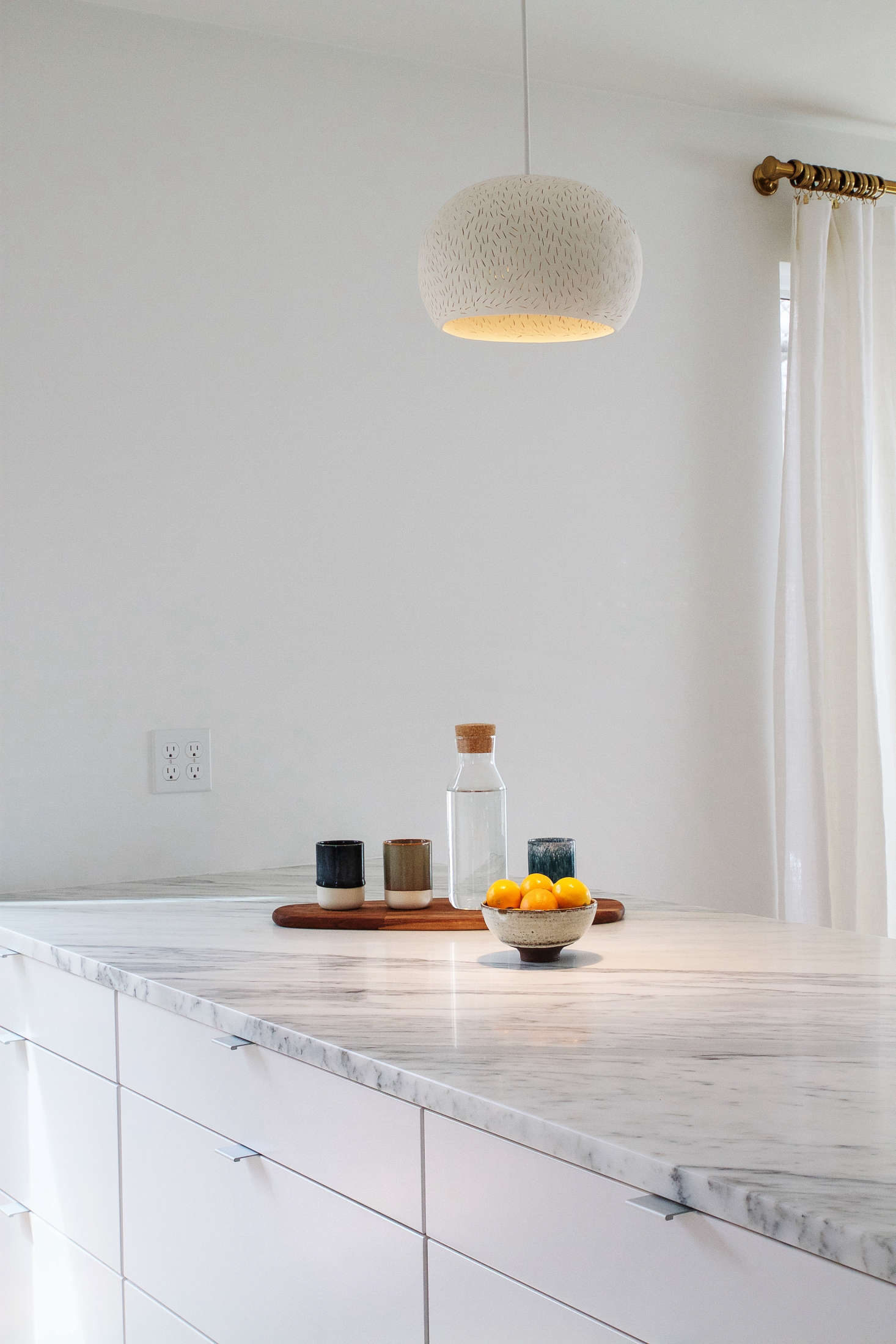 Creating a kitchen to fit their tastes and budget involved a mix of high/low, such as the IkeaVeddingecabinets topped withArabescato Marble Countertops.
