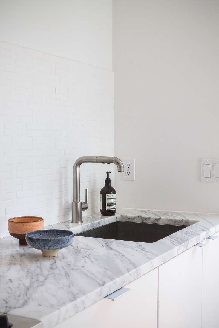 Armários brancos encontram paredes brancas e um backsplash branco em Reader Rehab: A Boston Kitchen Embraces the Light.