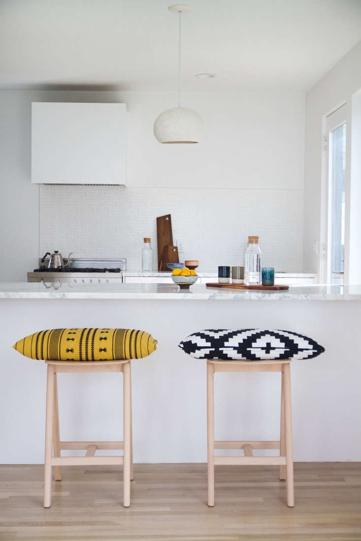 To encourage more interaction between the kitchen and dining/lounge area, the couple eliminated the walls separating the two rooms, replacing it with an open counter.
