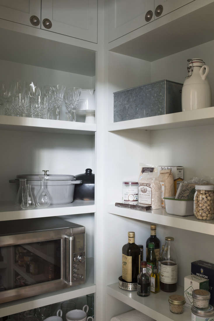 The walk-in pantry (opposite the refrigerator)is stocked with wine glasses, dry goods, and a freestanding microwave (powered by a built-in outlet).