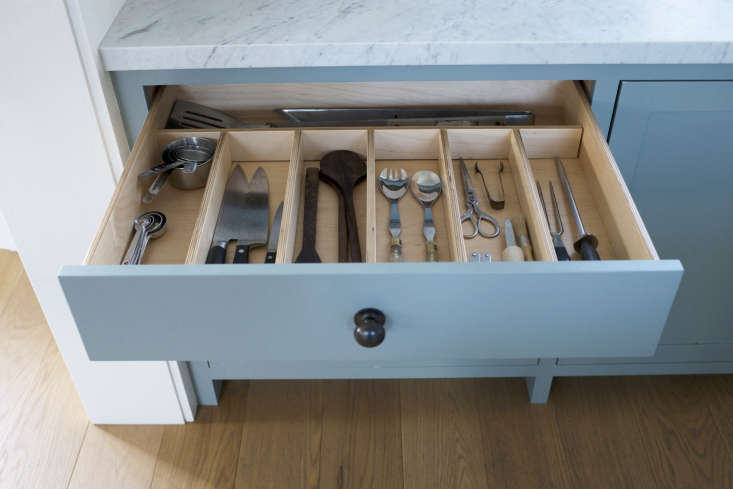 Kitchen prep essentials are organizedin a custom divided drawer to the left of the sink.