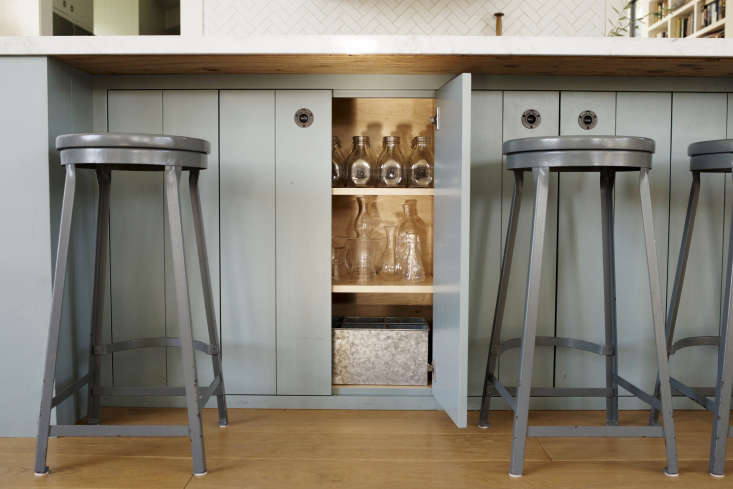 Vintagestools painted a glossy gray provide seating on the far side of the island, and shiplap cabinet doors hide additionalstorage.