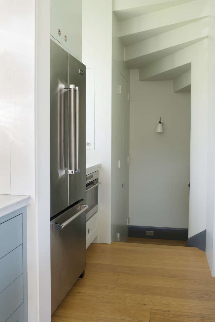 In the hallway off the kitchen, aViking French Door Refrigerator and coffee stationface an open pantry. Down the steps, a broom closet is tucked away; the space is illuminated by a Hector Wall Sconce from Original BTC.