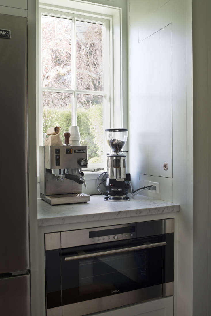 A Rancilio Silvia Espresso Machine stocks the coffee nook next to the refrigerator. Thebroom closet is justbeyond the frame, to the right.