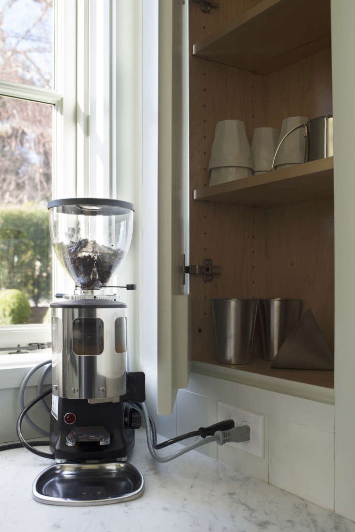 AMazzer Luigi Coffee Grindersits next to a built-in cabinet with adjustable shelves containingthe coffee-making basics.