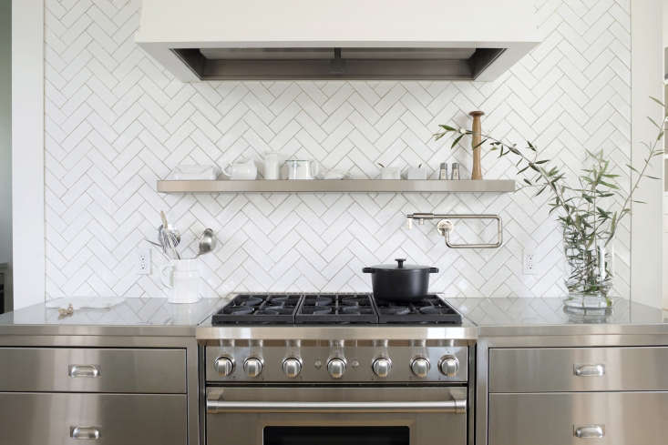 In the cooking zone, a 36-Inch Six-Burner Wolf Range isflanked by stainless steel drawers and countertops with a herringbone tile backsplash.