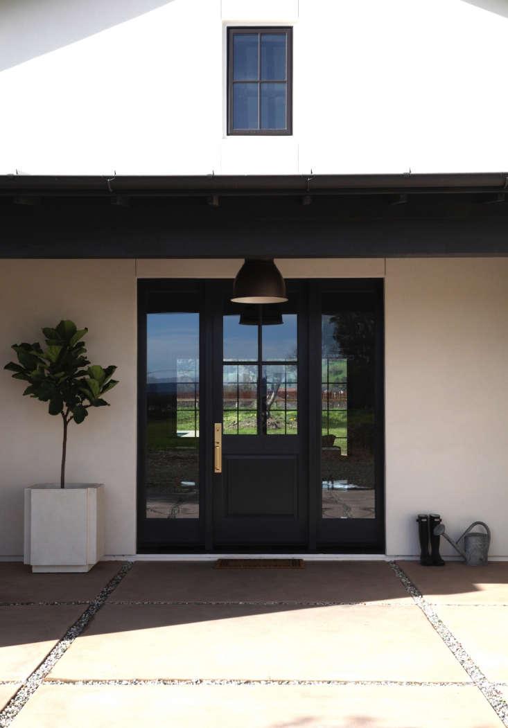 exterior black door pendant light white facade 1
