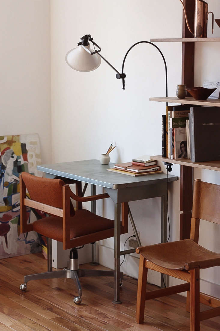 In the office, an industrial desk and chair are illuminated by a flea-market find.