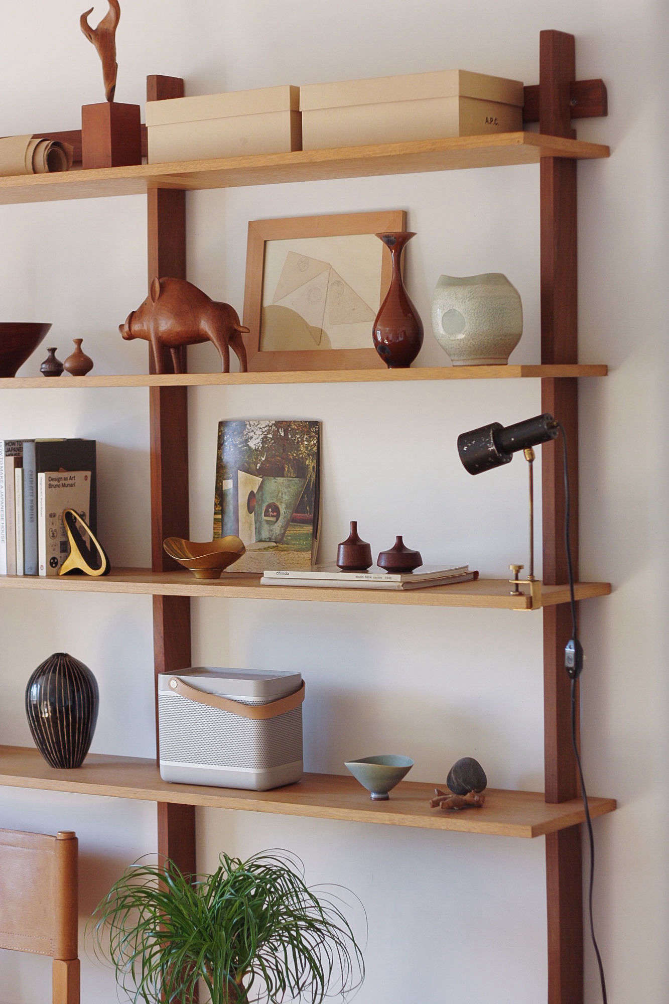Playful midcentury modern pieces rest on Sticotti Shelving from Design Within Reach.