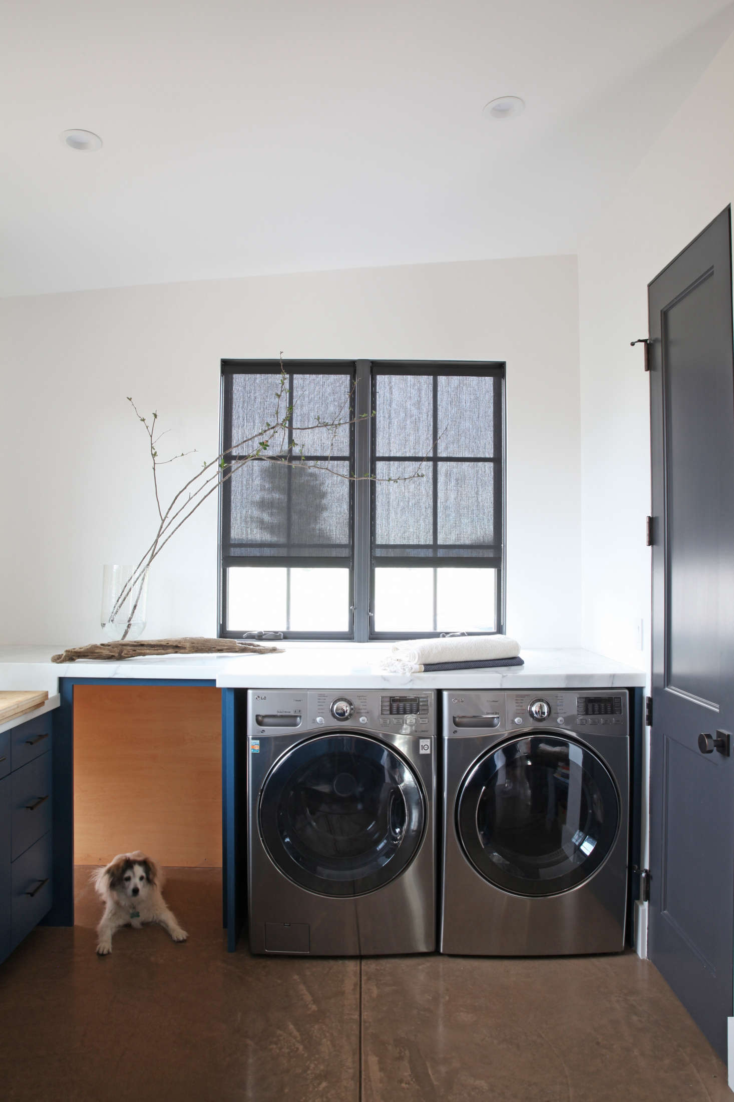 Stainless steel machines add to the clean-lined, sleek feel of the laundry room in A Modern Farmhouse for a Brit and a Texan.