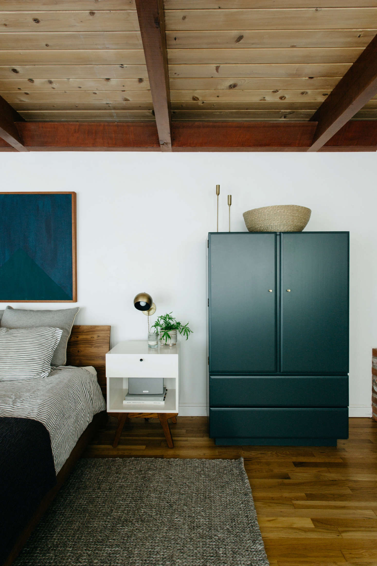 Nye had a vintage armoire refinished in Dark Pewter by Benjamin Moore with subtle brass hardware from Schoolhouse Electric. Thedark blue painting above the bed is Courtney Nye&#8