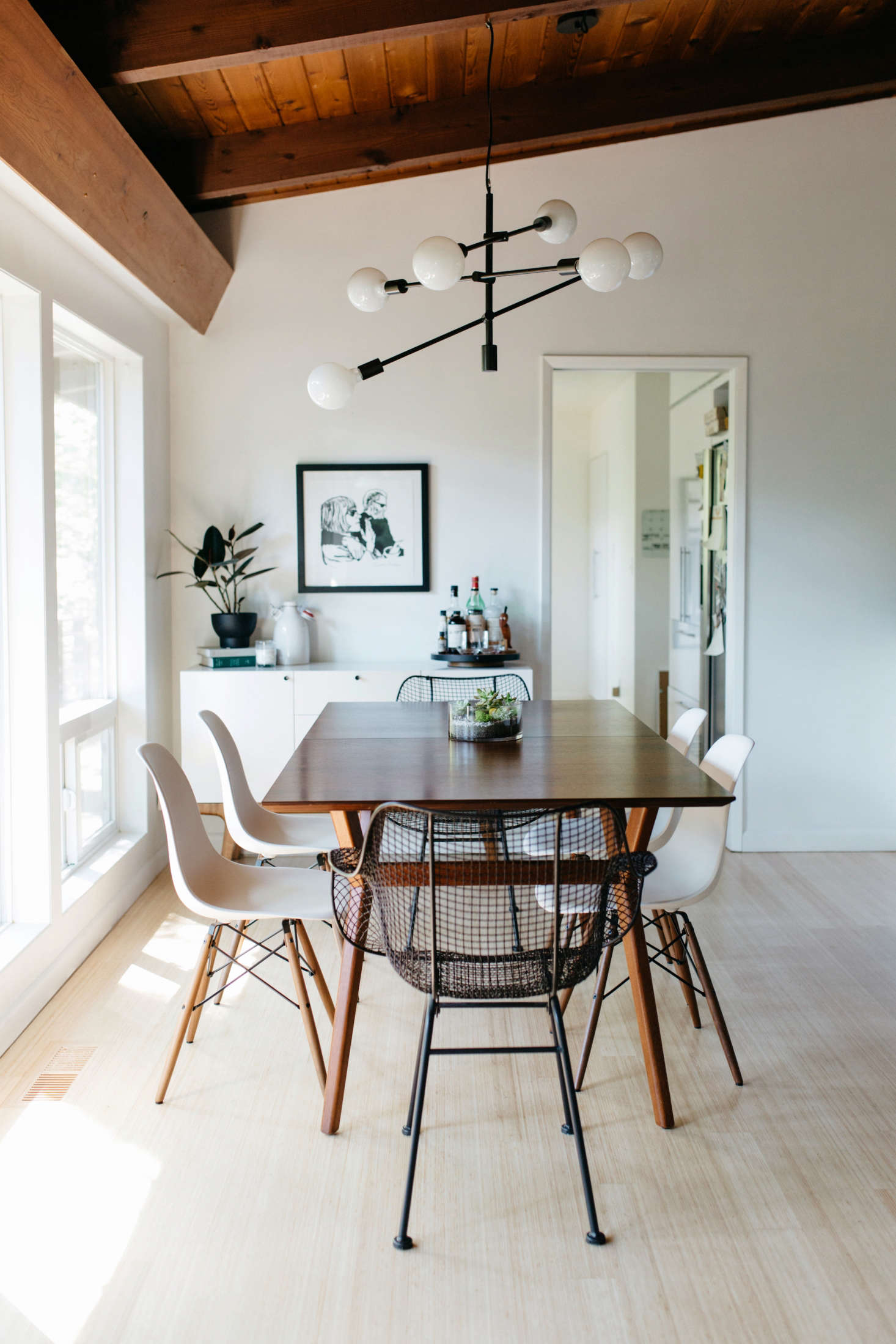 A Mid-Century Expandable Dining Table from West Elm is flanked by four Eames Molded Plastic Dowel-Leg Side Chairs.Above the table hangs aMobile Chandelier from West Elm.