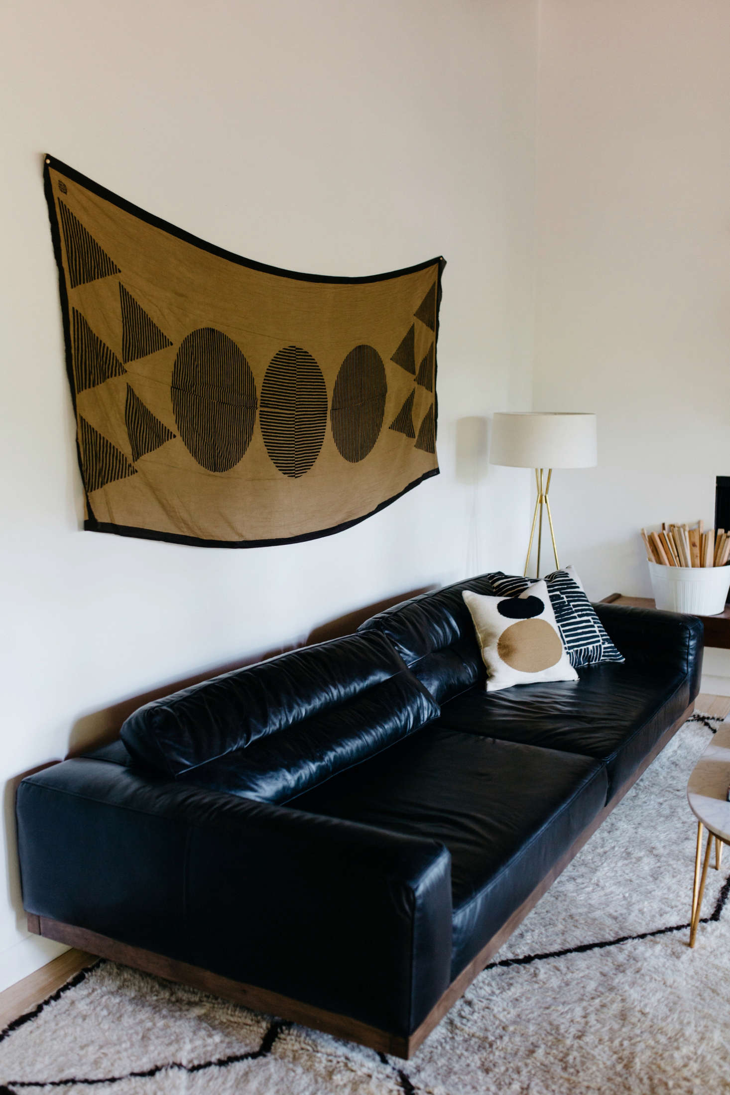ATemple print from Block Shop Textileshangs above theblack leather sofa from Four Hands.