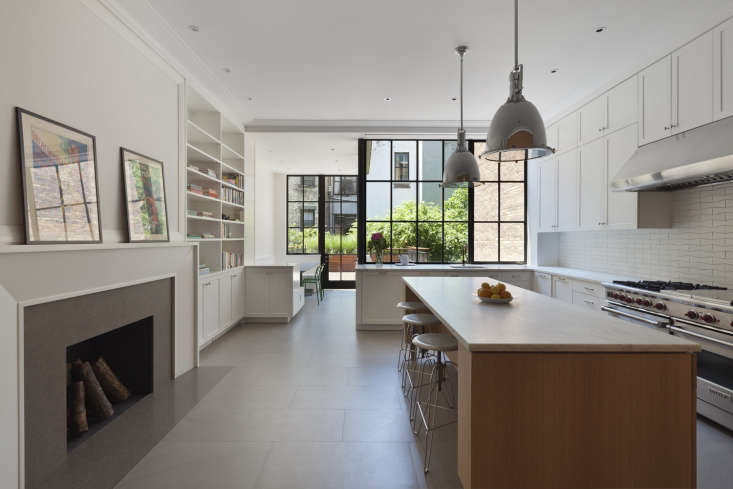 A streamlined fireplace and island face an expansive L-shaped kitchen in a New York brownstone by architecture firm O&#8