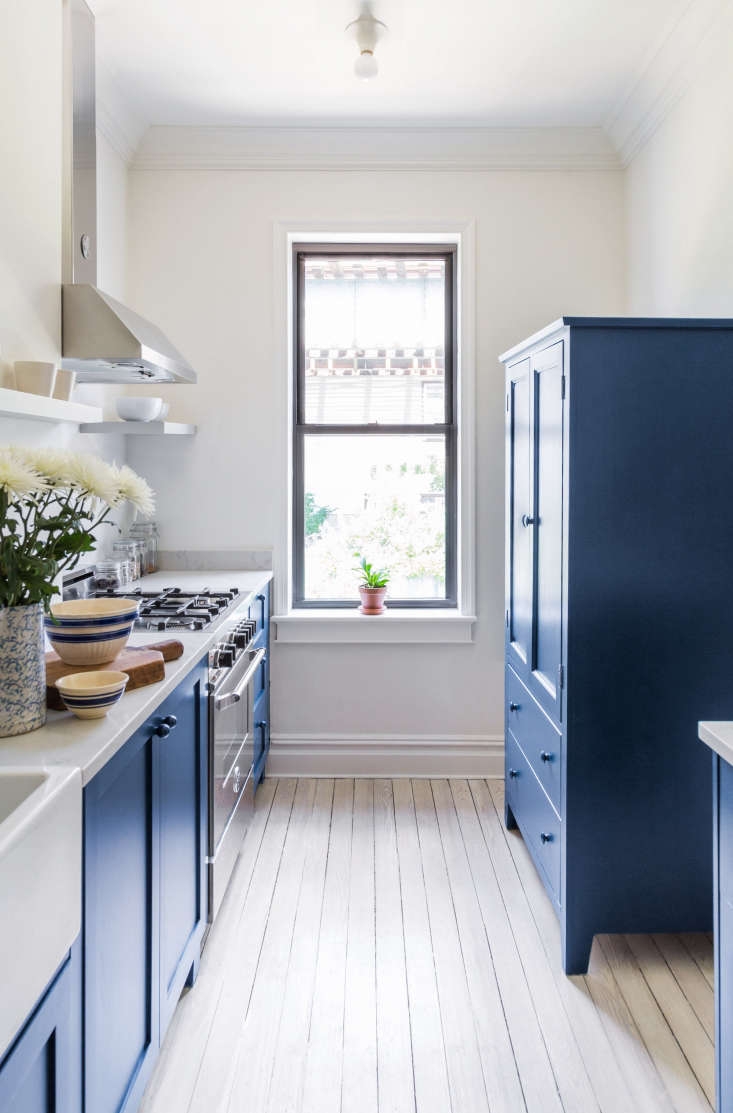 Opposite the Bertazzoni range is a cupboard that acts as the pantry in the narrow kitchen. Photograph by White Arrow from Before and After: A Buzzfeed Founder's Renovated Rowhouse, Budget Edition.